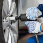 mechanic-with-screwdriver-changing-car-tire-P8D5VFA-crop